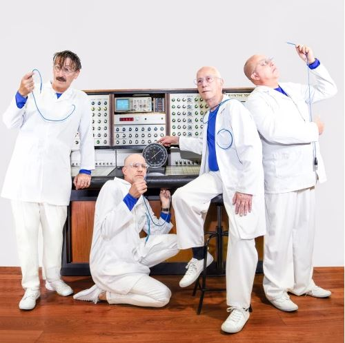 Four musicians dressed in white coats as doctors in front of the Synthi 100