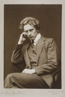 Photograph of young adult Percy Grainger wearing a tweed suit, seated, resting his head on his right hand with his left in his lap. Dover Street Studios, London. Sepia-toned silver gelatin print.